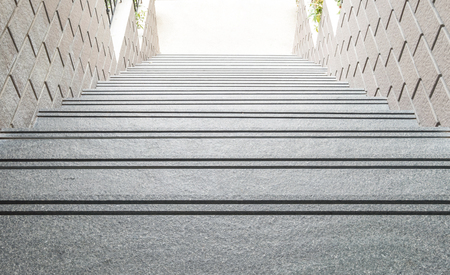 Superb Closeup Down Step Pattern Of Stone Stair With Blurred Stone Brick Wall  Textured Background Under Sunlight