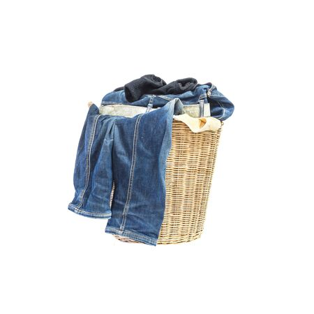 used clothes: Closeup wood weave basket for used clothes with pile of clothes in house isolated on white background