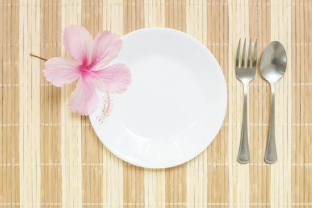 discus: Closeup white ceramic dish with stainless fork and spoon with pink flower on wood mat textured background on dining table in top view
