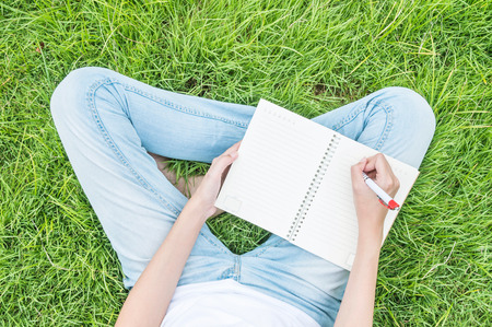 writes: Closeup asian woman sitting on grass field textured background for writing on note book under day light in the garden Stock Photo