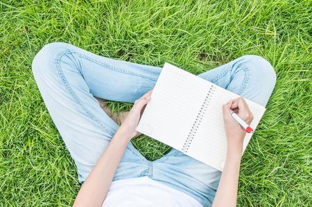 schreiben: Closeup asiatische Frau sitzt auf Gras Feld strukturierten Hintergrund für das Schreiben auf Notizbuch unter Tageslicht im Garten