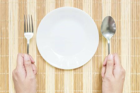 discus: Closeup white ceramic dish with stainless fork and spoon in woman hand on wood mat textured background on dining table in top view