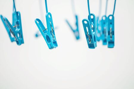 Closeup colorful hanged blue clothespin for dry clothes in the sun on blurred white cement textured background in selective focus
