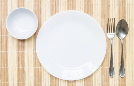 slick: Closeup white ceramic dish and cup with stainless fork and spoon on wood mat textured background on dining table in top view , group of tableware before dinner Stock Photo