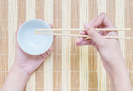 discus: Closeup white ceramic chalice with blurred wood chopsticks in woman hand on wood mat textured background on dining table in top view in eating concept