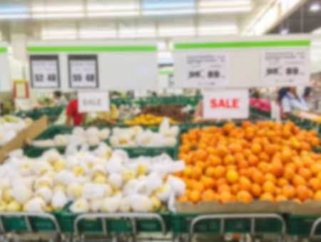 light duty: Motion blur of fruit shelves for sale in supermarket with some people shopping