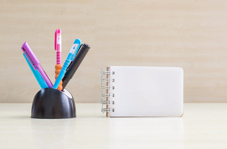 desk tidy: Closeup color pen with black ceramic desk tidy for pen and white page at the note book on blurred wood desk and wood wall textured background