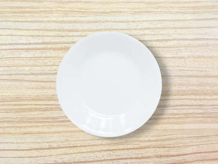 discus: Closeup white ceramic dish on wood dining table textured background in top view Stock Photo