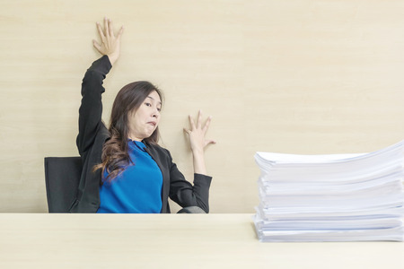 Closeup joke action of working woman are afraid pile of work paper in front of her in work concept on blurred wooden desk and wooden wall textured background in the meeting room