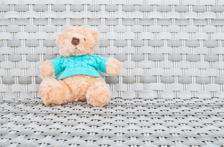 kids weaving: Closeup a fabric bear doll sit on wood weave chair texture background with copy space