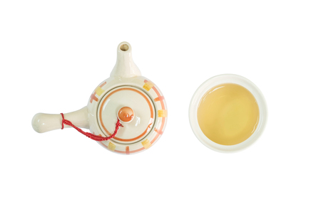 Closeup ceramic tea pot and tea cup with brown tea isolated on white background