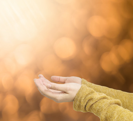 act of god: Closeup action of woman hold out hand to wait for good things on abstract blurred brown light spot bokeh textured background