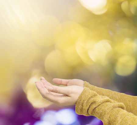 act of god: Closeup action of woman hold out hand to wait for good things on abstract blurred colorful light spot bokeh textured background