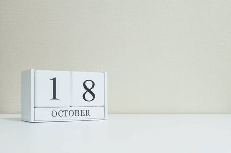 cream color: Closeup white wooden calendar with black 18 october word on blurred white wood desk and cream color wallpaper in room textured background with copy space , view another more date in my portfolio