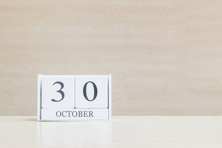 wooden surface: Closeup surface white wooden calendar with black 30 october word on blurred brown wood desk and wood wall textured background with copy space , selective focus at the calendar