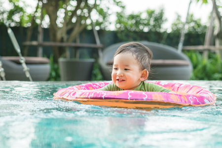 Closeup asian baby boy sit in a boat for children in the swimming pool background with smile face in happy emotion