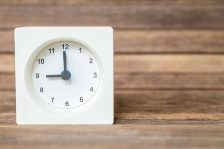 showed: Closeup white clock showed nine oclock on blurred brown wood board background Stock Photo