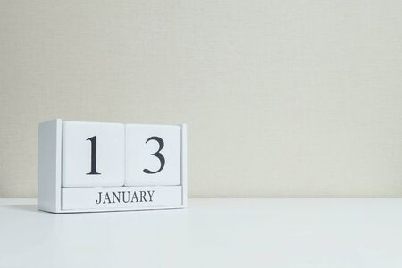 thirteen: Closeup white wooden calendar with black 13 january word on blurred white wood desk and cream color wallpaper in room textured background with copy space , selective focus at the calendar
