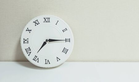 Closeup white clock for decorate show a quarter past seven or 7:15 a.m. on white wood desk and cream wallpaper textured background with copy space