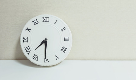 Closeup white clock for decorate show half past seven or 7:30 a.m. on white wood desk and cream wallpaper textured background with copy space Stock Photo