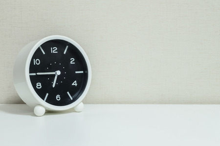 dial plate: Closeup black and white alarm clock for decorate in a quarter to seven or 6:45 a.m. on white wood desk and cream wallpaper textured background with copy space