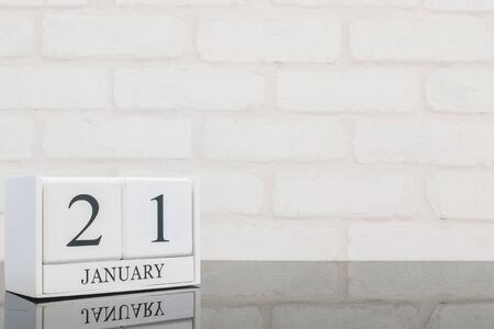 textured: Closeup white wooden calendar with black 21 january word on black glass table and white brick wall textured background with copy space , selective focus at the calendar
