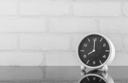 oclock: Closeup black and white alarm clock for decorate in 8 oclock on black glass table and white brick wall textured background in black and white tone with copy space Stock Photo