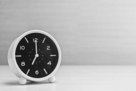 seven o'clock: Closeup alarm clock for decorate in 7 oclock on wood desk and wall textured background in black and white tone with copy space