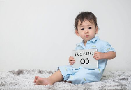 Closeup cute asian kid show calendar on plate in his hand in february 5 word on gray carpet and white cement wall textured background with copy space