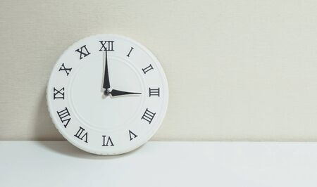 Closeup white clock for decorate show 3 o'clock on white wood desk and cream wallpaper textured background with copy space