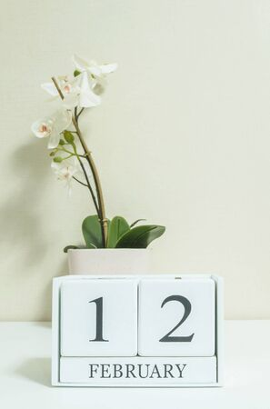 Closeup white wooden calendar with black 12 february word with white orchid flower on white wood desk and cream color wallpaper in room textured background in selective focus at the calendar