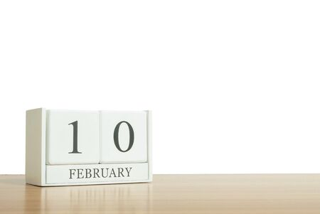 Closeup surface white wooden calendar with black 10 february word on blurred brown wood desk isolated on white background with copy space , selective focus at the calendar