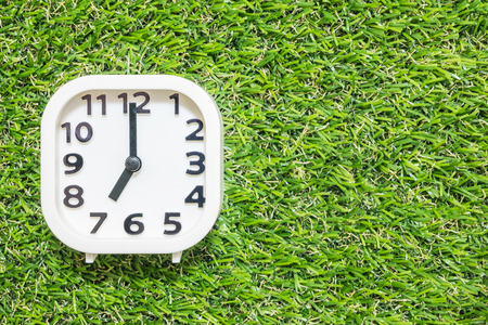 Closeup white clock for decorate in 7 oclock on green artificial grass floor textured background with copy space