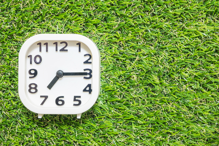 Closeup white clock for decorate show a quarter past seven or 7:15 a.m. on green artificial grass floor textured background with copy space