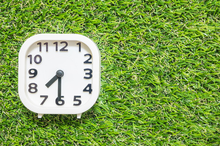 Closeup white clock for decorate show a half past seven or 7:30 a.m. on green artificial grass floor textured background with copy space Standard-Bild