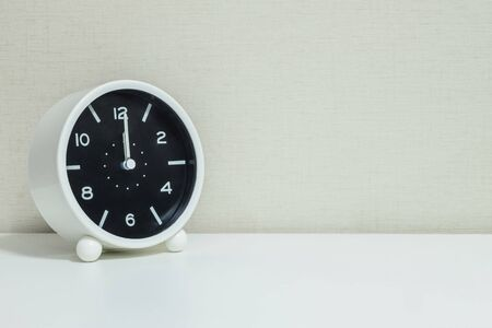mid afternoon: Closeup black and white alarm clock for decorate in 12 oclock on white wood desk and cream wallpaper textured background with copy space