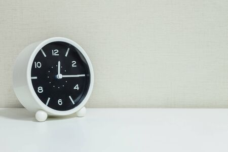 mid afternoon: Closeup black and white alarm clock for decorate show a quarter past twelve or 12:15 a.m.on white wood desk and cream wallpaper textured background with copy space Stock Photo