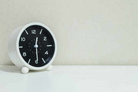飾るショー ショー 12:30 または 12:30 白木製デスク、コピー スペースを持つ質感のクリームの壁紙の背景の黒と白のクローズ アップ目覚まし時計 写真素材