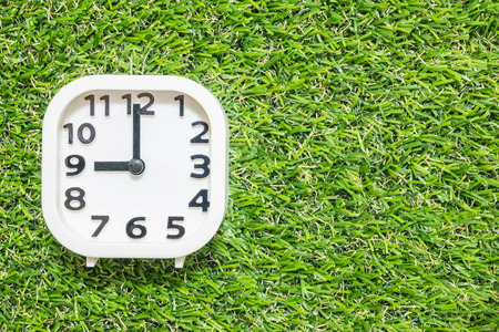 Closeup white clock for decorate in 9 oclock on green artificial grass floor textured background with copy space
