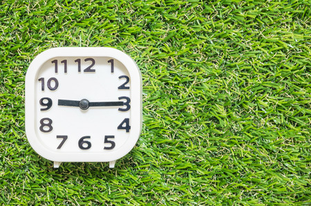 Closeup white clock for decorate show a quarter past nine or 9:15 a.m. on green artificial grass floor textured background with copy space