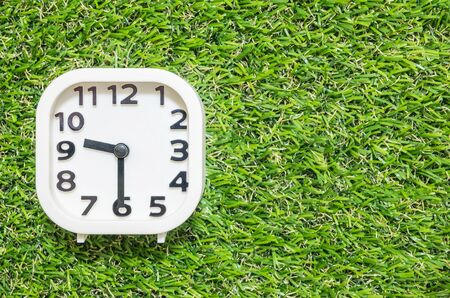 Closeup white clock for decorate show a half past nine or 9:30 a.m. on green artificial grass floor textured background with copy space Stock Photo
