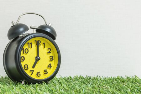 Closeup black and yellow clock for decorate in 7 oclock on green artificial grass floor and cream wallpaper textured background with copy space Stock Photo