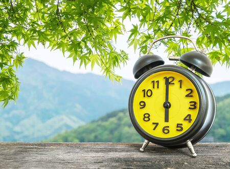 pm: Closeup black and yellow alarm clock for decorate in 6 oclock on blurred leaves and mountain view background Stock Photo