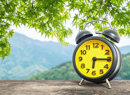 pm: Closeup black and yellow alarm clock for decorate show a quarter past six or 6:15 a.m. on blurred leaves and mountain view background Stock Photo