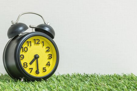Closeup black and yellow alarm clock for decorate show half past seven or 7:30 a.m. on green artificial grass floor and cream wallpaper textured background with copy space