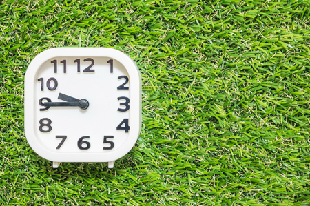 Closeup white clock for decorate show a quarter to ten or 9:45 a.m. on green artificial grass floor textured background with copy space