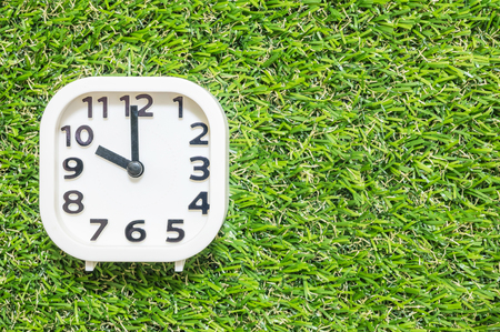 pm: Closeup white clock for decorate in 10 oclock on green artificial grass floor textured background with copy space