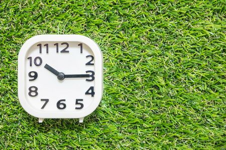 Closeup white clock for decorate show a quarter past ten or 10:15 a.m. on green artificial grass floor textured background with copy space