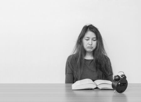 Closeup asian woman sitting for read a book with boring face emotion on wood table and white cement wall textured background in black and white tone with copy space