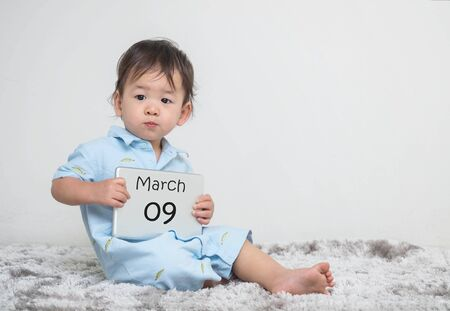 Closeup cute asian kid show calendar on plate in his hand in march 9 word on gray carpet and white cement wall textured background with copy space Stock Photo